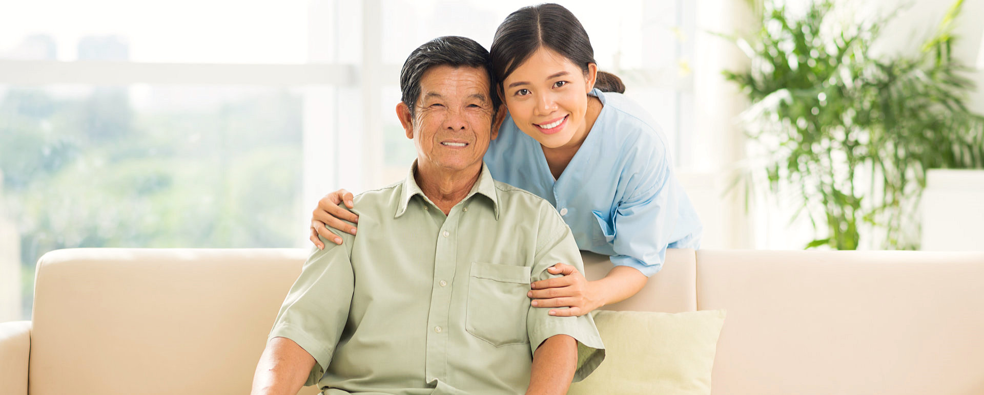 senior man and female caregiver smiling