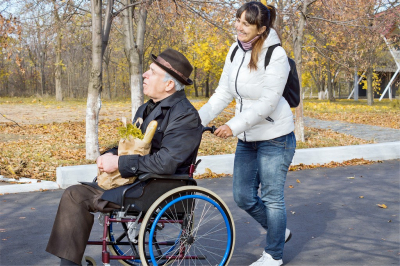 senior man on wheelchair with caregiver strolling outside